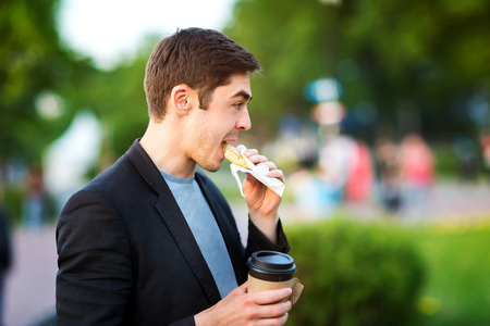 Closeup portrait of hipster man eating pastry and holding coffee at green park background. Фото со стока