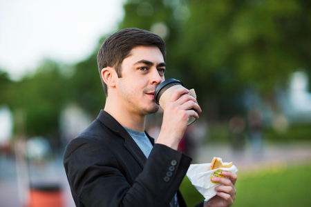 Closeup portrait of businessman holding pastry and drinking coffee at green park background.