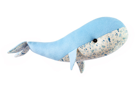 Closeup image of blue toy whale pillow with ornament isolated at white background.