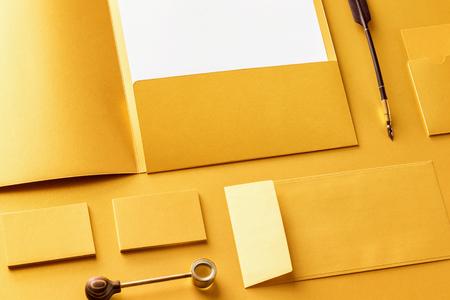 Corporate stationery set mockup. Presentation folder, letterhead, envelope and business cards at golden textured foil paper background. 版權商用圖片