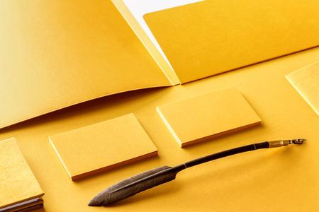 Corporate stationery set mockup. Presentation folder, letterhead and business cards at golden textured foil paper background.