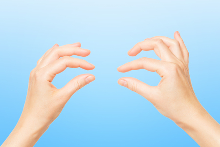Females hands holding invisible object isolated at blue background.