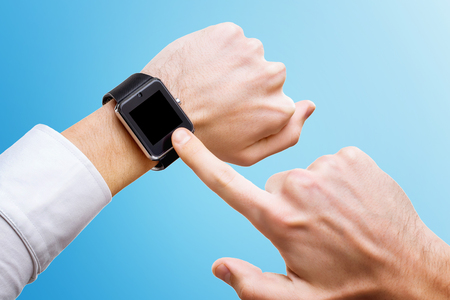 Businessman is pointing at smart hand with smart watch isolated at blue background. Stock Photo