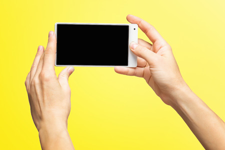 Mockup of female hands holding white frameless cellphone with black screen and making selfie at isolated yellow background.