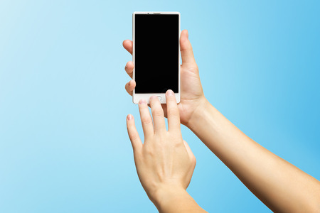 Mockup of female hands holding modern white cellphone with black screen and making sliding gesture isolated at blue background.