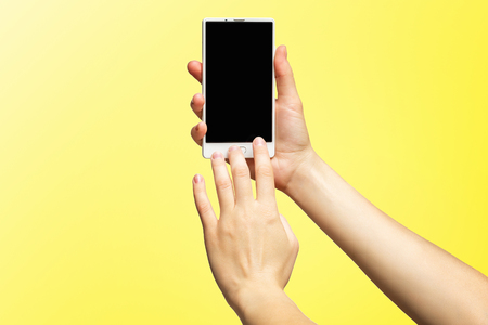 Mockup of female hands holding modern white cellphone with black screen and making sliding gesture isolated at yellow background. Kho ảnh