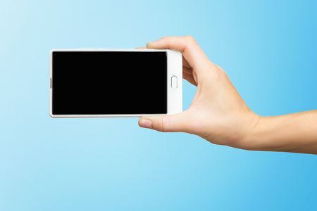 Mockup of female hand holding white frameless cell phone with black screen isolated at blue background. Kho ảnh