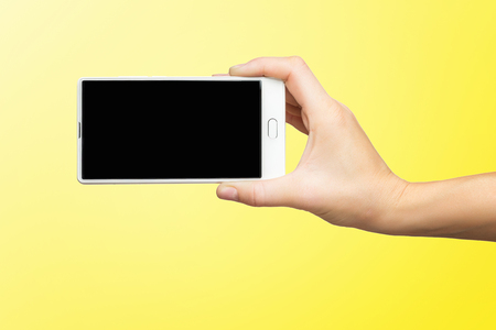 Mockup of female hand holding white frameless cell phone with black screen isolated at yellow background.