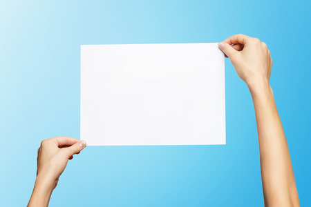 Mockup of female hands holding blank paper list isolated at blue background. Kho ảnh