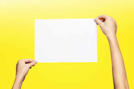 Mockup of female hands holding blank paper list isolated at yellow background.