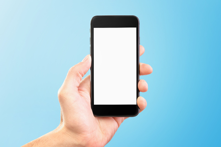 Male hand holding black cellphone isolated at bue background.