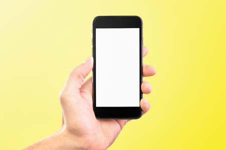 Male hand holding black cellphone isolated at yellow background.
