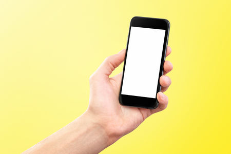 Mockup of male hand holding black cellphone isolated at yellow background.