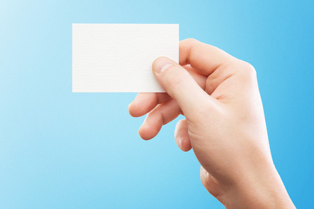 Male hand holding white business card at isolated blue background mockup.