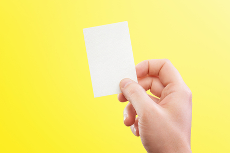 Male hand holding white business card at isolated yellow background mockup. Kho ảnh