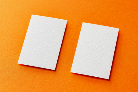 Mock up of two vertical white blank business cards isolated at orange paper background.