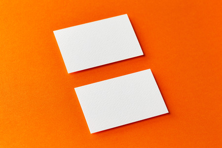 Mock up of two horizontal white blank business cards isolated at orange paper background.