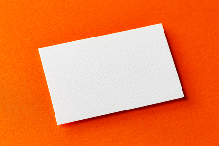 Mockup of single white business card isolated at orange textured design paper background.