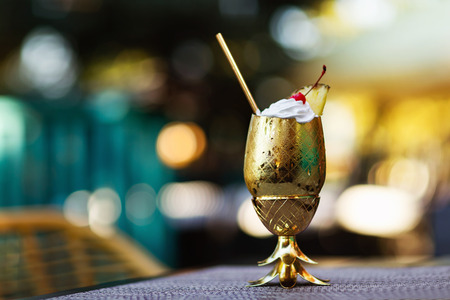 Closeup pina colada cocktail served in metal golden color glass looking like pineapple at bar background.