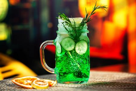 Closeup jar of cucumber and tarragon lemonade served with orange chips at bar background.