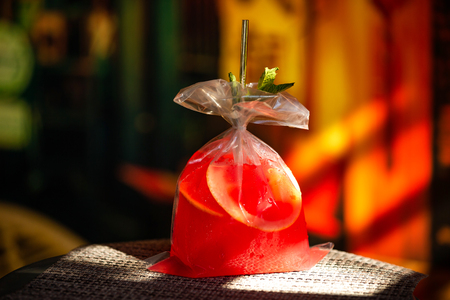 Red strawberry cocktail served in a plastic bag at colorful bar background.