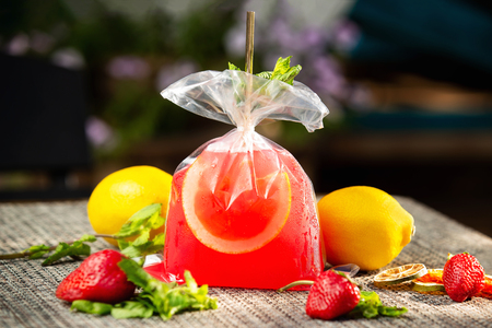 Red strawberry lemonade served in a plastic bag with lemons around at bar background.