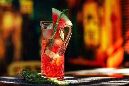 Closeup jug of watermelon sangria at colorful bar background.