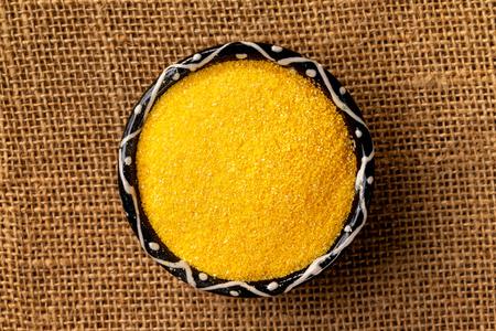 Closeup top view bowl of raw polenta corn at centre of sack cloth background. Stock Photo