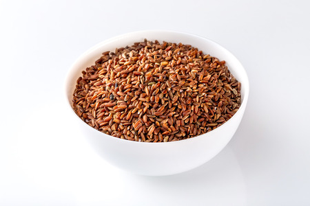 Bowl of red raw rice isolated at white background. Stock Photo