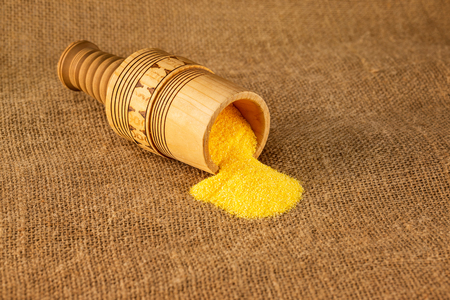 Closeup wooden mortar with raw vegetarian polenta grains at sacking background.