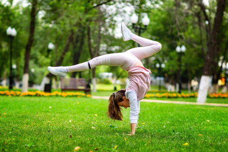 Young woman is making fitness standing on hands at summer park background. Stock Photo