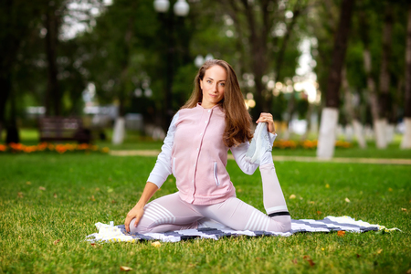 Young woman is making fitness sstretching a leg at summer park background.