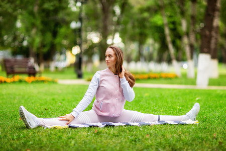Young woman is making fitness  split exercise at summer park background. Stock Photo