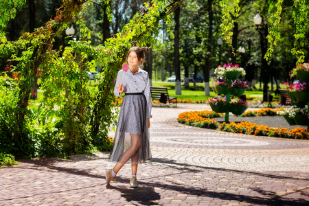 Young elegant girl is holding lollipop at summer park background.