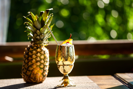 Closeup pina colada cocktail served in metal golden color glass and a pineapple fruit at green background.