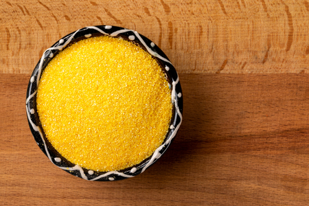 Closeup top view bowl of raw polenta cornmeal at left corner of wooden background.