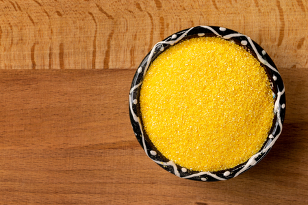 Closeup top view bowl of raw polenta cornmeal at right corner of wooden background. Stock Photo