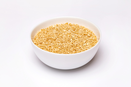 Closeup bowl of brown raw rice isolated at white background. Foto de archivo