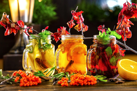 Ice tea jars with fruits decorated with rowan branches at wooden table background. Фото со стока