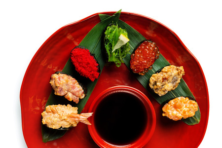 Top view plate of sushi set served with sauce isolated at white background. Stock Photo