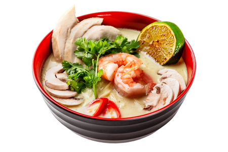 Bowl of thai tom yum soup isolated at white background.