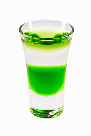 Closeup glass of green fairy layered cocktail shot with absinthe isolated at white background. Stock Photo