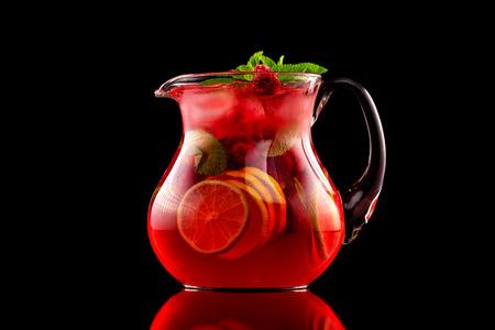 Pot en verre de sangria au vin rouge avec des baies sauvages et un mélange d'agrumes isolé sur fond noir.