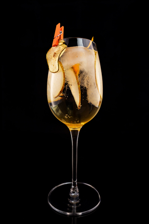 Glass of fizz cocktail with white sparkling wine and pear decorated with lemon chips isolated at black background.