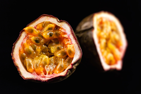 Macro image of two halves of passion fruit isolated at black background. Stok Fotoğraf