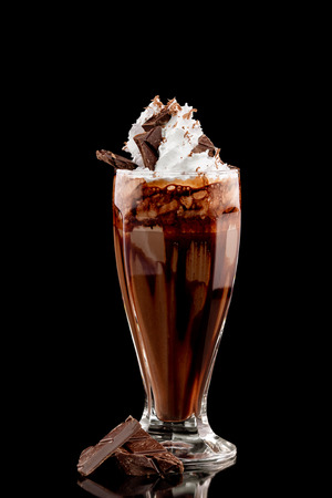 Closeup glass of chocolate milk shake decorated with whipped cream isolated at black background.