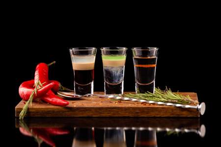 Three alcohol shooter layered cocktails on a wooden board served with barman spoon and chili pepper isolated at black background. Standard-Bild - 111416239