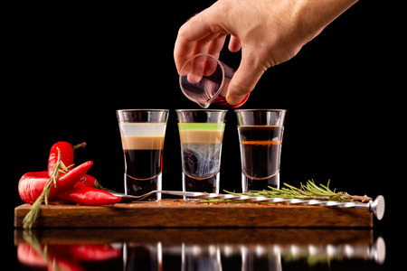 Three alcohol shooter layered cocktails on a wooden board served with barman spoon and chili pepper isolated at black background. Barman is making hiroshima cocktail. Standard-Bild - 111416241