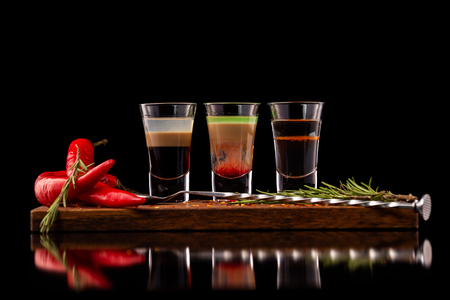 Three alcohol shooter layered cocktails on a wooden board served with barman spoon and chili pepper isolated at black background. Standard-Bild - 111416243