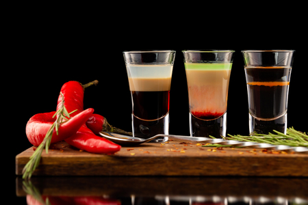 Three alcohol shooter layered cocktails on a wooden board served with barman spoon and chili pepper isolated at black background. Stock fotó